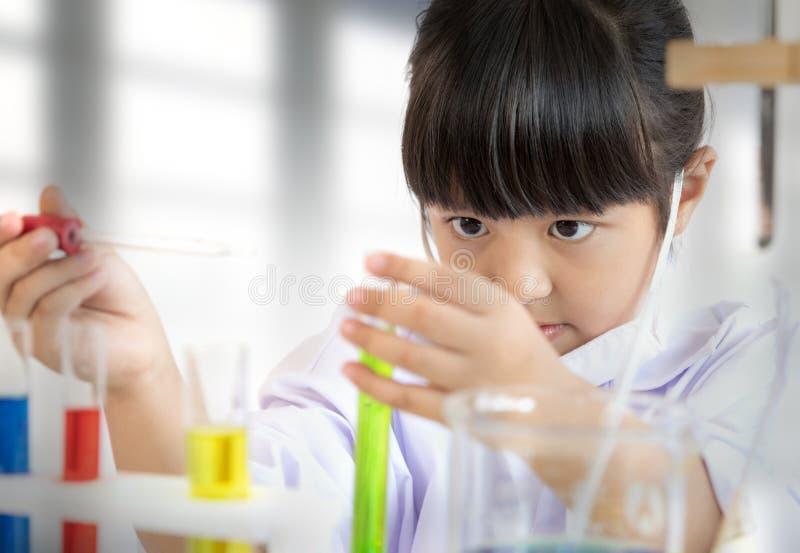 Muchacha asiática que hace el prueba de laboratorio con los tubos coloridos imágenes de archivo libres de regalías