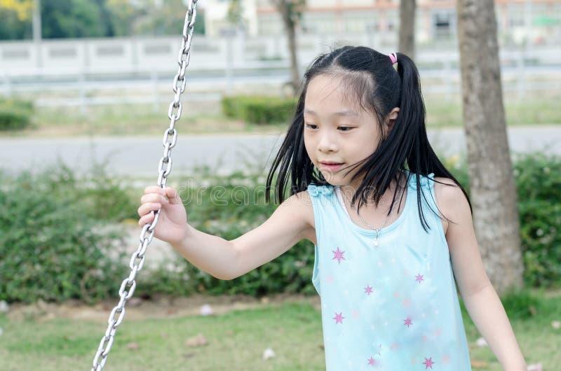 Muchacha asiática que lleva a cabo el oscilación de cadena en el parque fotos de archivo libres de regalías