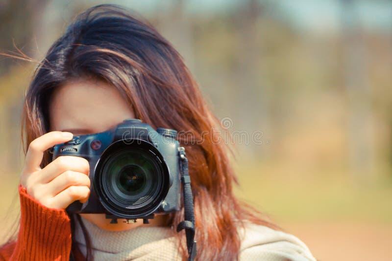 Muchacha asiática que lleva a cabo un camer digital foto de archivo libre de regalías