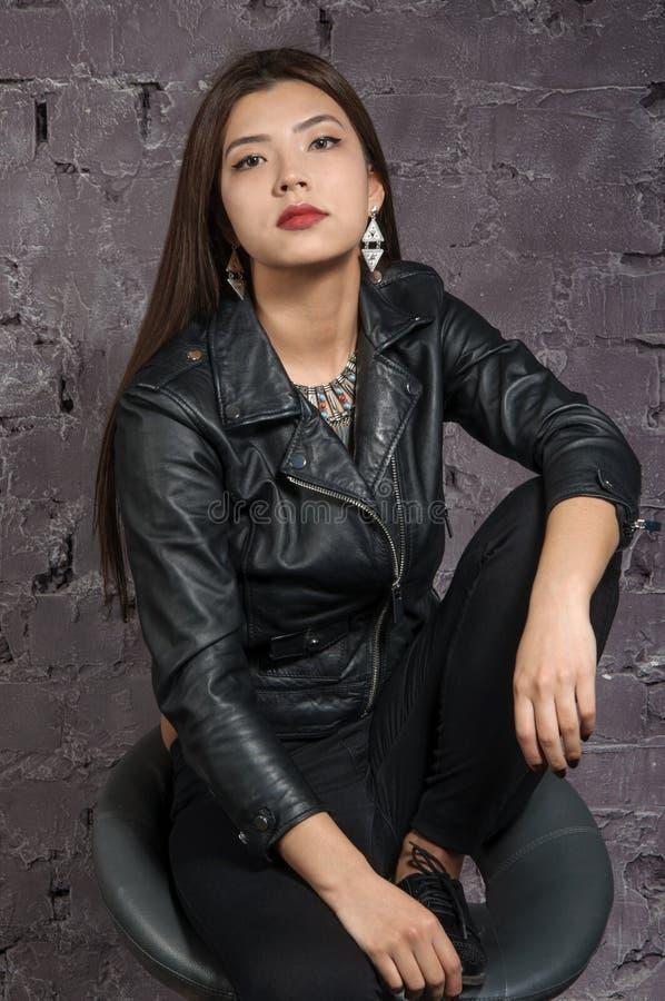 Muchacha asiática que lleva una chaqueta negra imagen de archivo
