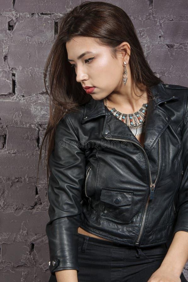 Muchacha asiática que lleva una chaqueta negra foto de archivo libre de regalías