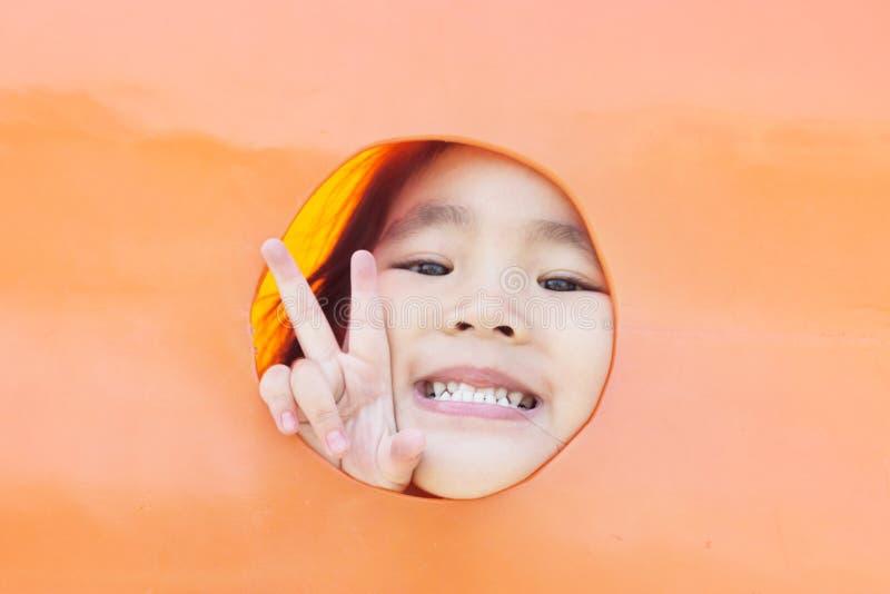 muchacha asiática que mira fuera del agujero plástico imagenes de archivo