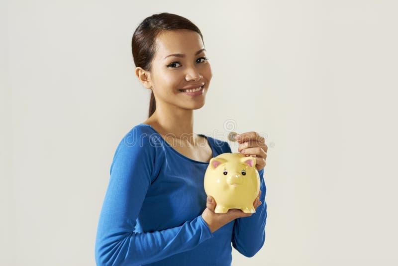 Muchacha asiática que muestra la moneda del piggybank y del euro fotos de archivo