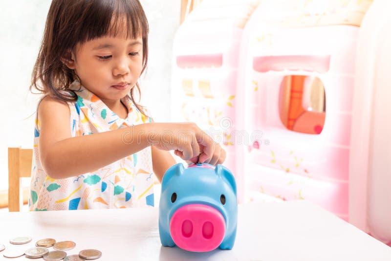 Muchacha asiática que pone la moneda en la hucha para el dinero de ahorro Foco selectivo de la mano del niño imagenes de archivo