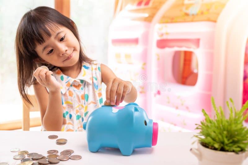 Muchacha asiática que pone la moneda en la hucha para el dinero de ahorro Foco selectivo de la mano del niño imagen de archivo