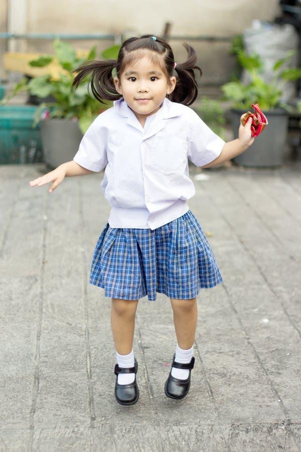 Muchacha asiática que salta en escuela uniforme imagen de archivo