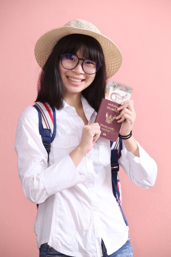 Muchacha asiática que sostiene el pasaporte y el billete de banco fotos de archivo