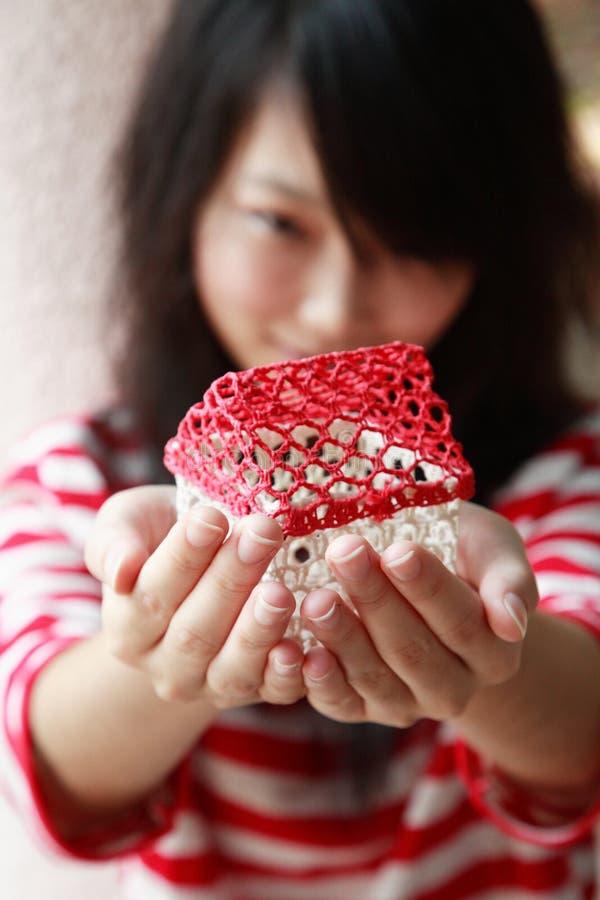 Muchacha asiática que sostiene la casa minúscula imagenes de archivo