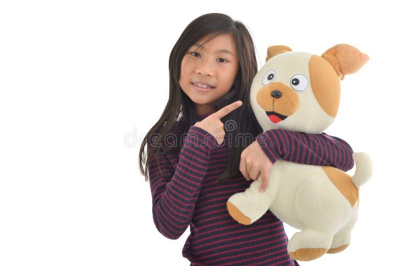 Muchacha asiática que sostiene la muñeca del perrito en blanco imagenes de archivo