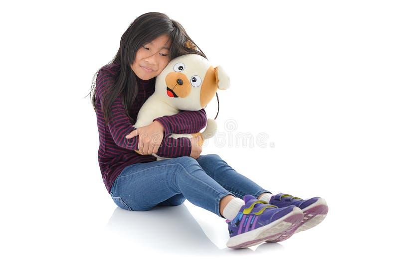 Muchacha asiática que sostiene la muñeca del perrito en blanco fotografía de archivo libre de regalías