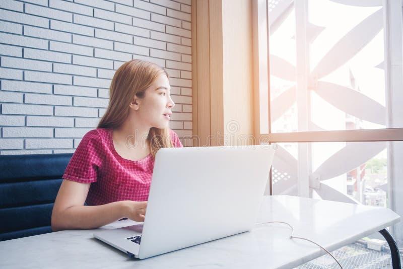 Muchacha asiática que trabaja en una cafetería con un ordenador portátil freelan femenino foto de archivo libre de regalías
