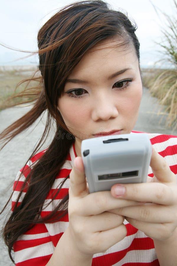 Muchacha asiática que usa su PDA imagen de archivo libre de regalías