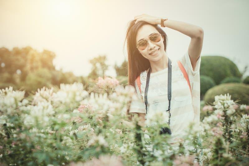 Muchacha asiática relajarse para disfrutar de día de fiesta con la afición de la flor de la fotografía en el parque fotografía de archivo