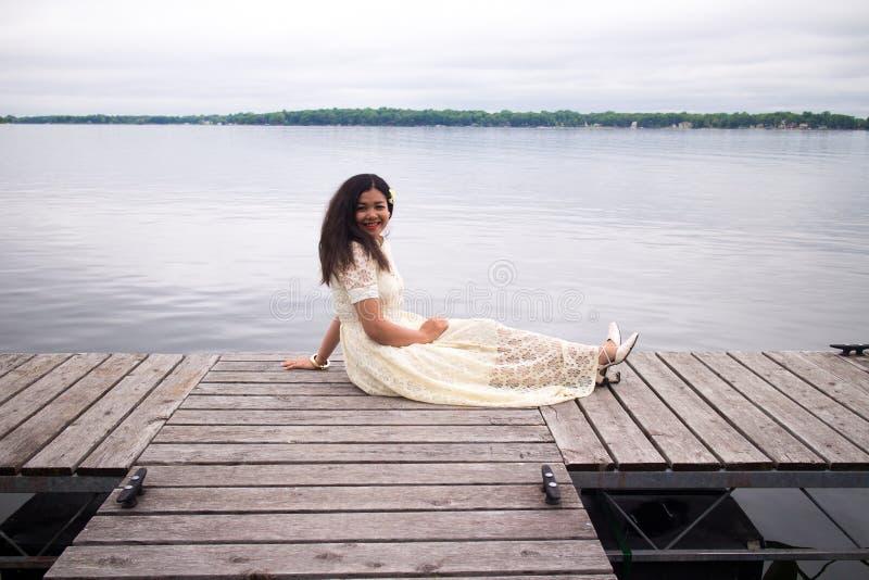 Muchacha asiática sonriente en un vestido blanco que se sienta en un muelle imagen de archivo
