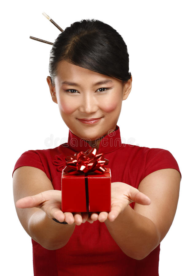 Muchacha asiática tradicional que muestra un regalo de la Navidad fotos de archivo