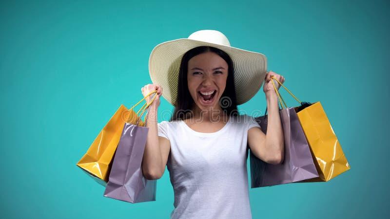 Muchacha asi?tica alegre en Panam? que sostiene muchas bolsas de papel, compras, afici?n para mujer imagen de archivo libre de regalías