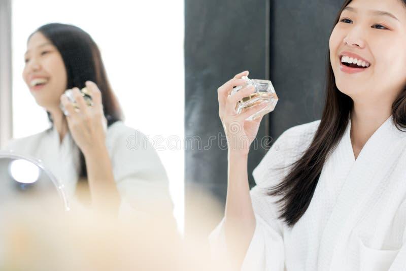 Muchacha asi?tica con el perfume, la mujer joven aplicando perfume en su mu?eca y oler foto de archivo