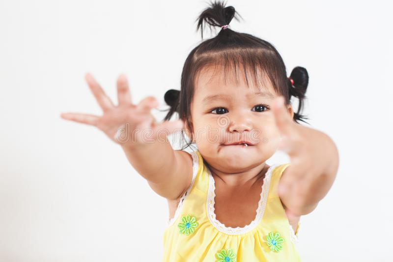 Muchacha asi?tica del ni?o del beb? que come los tallarines sola y que hace un l?o en su cara y mano imagenes de archivo