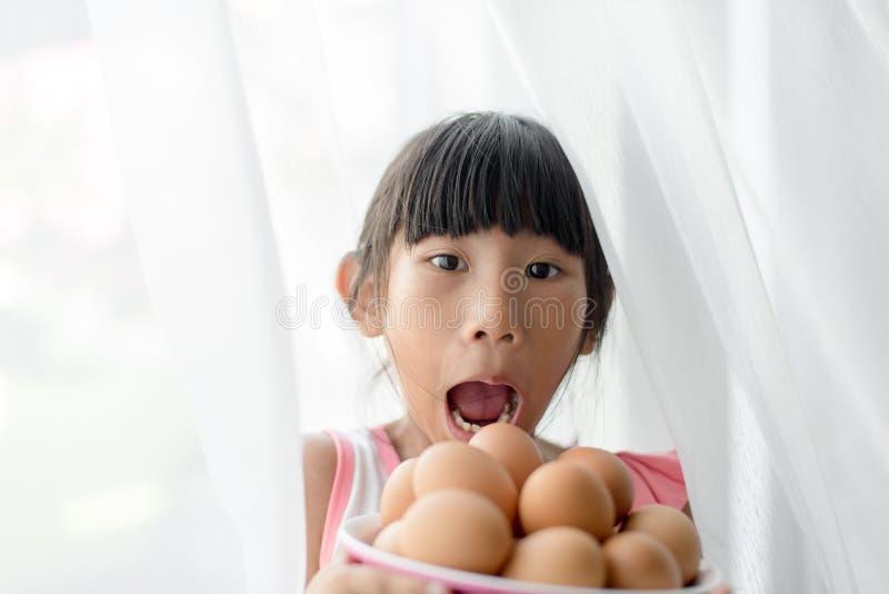 Muchacha asombrosamente que sostiene el cuenco de los huevos con blanco imágenes de archivo libres de regalías