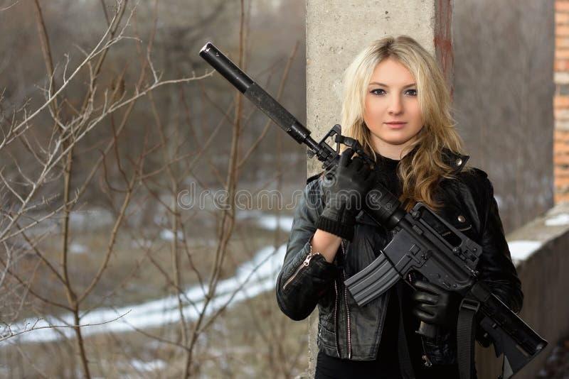 Muchacha asustada con un rifle fotografía de archivo libre de regalías