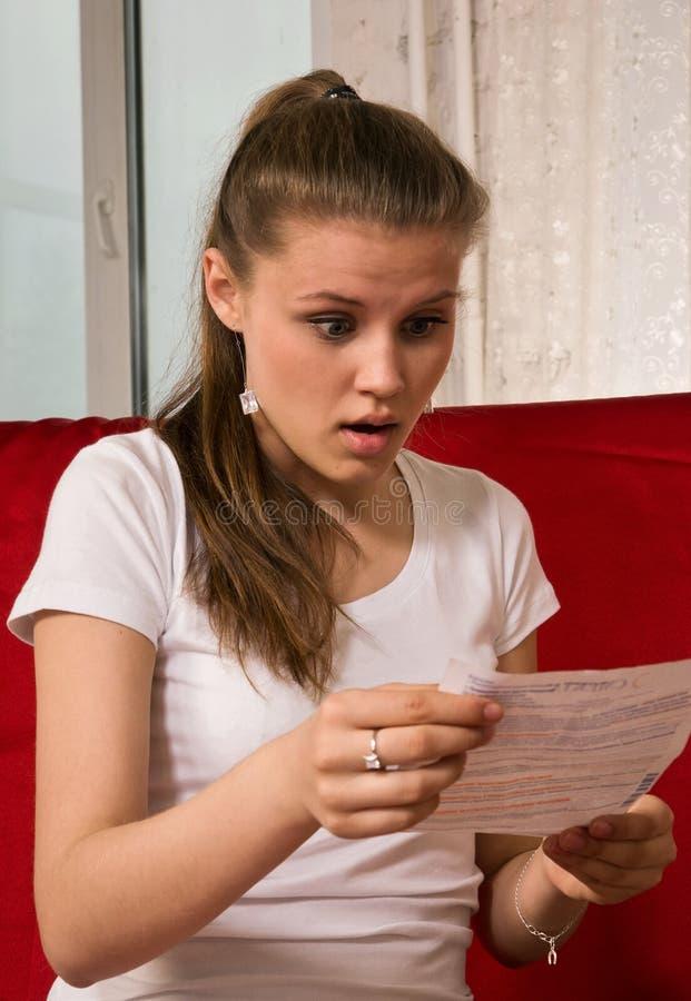 Muchacha asustada que lee una instrucción de la medicina foto de archivo