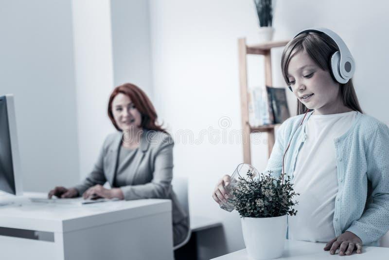 Muchacha atenta en planta de riego de los auriculares en oficina fotos de archivo libres de regalías