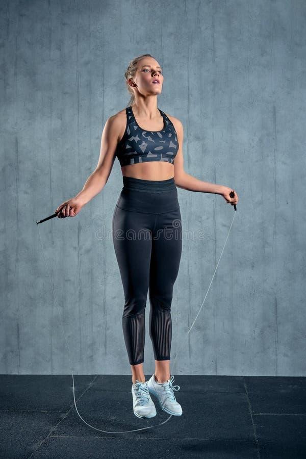 Muchacha atlética alegre en el entrenamiento de la mujer de la ropa de deportes con una cuerda que salta en un gimnasio en una pa fotos de archivo