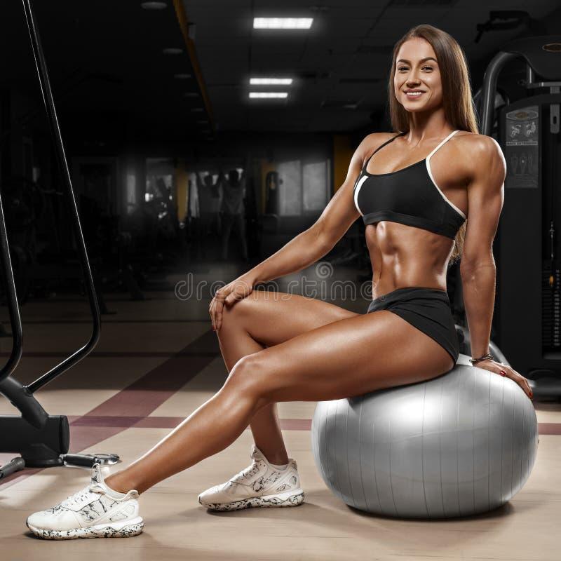 Muchacha atlética atractiva que se resuelve en gimnasio La mujer de la aptitud se sienta en una bola de los pilates, ABS imagen de archivo libre de regalías