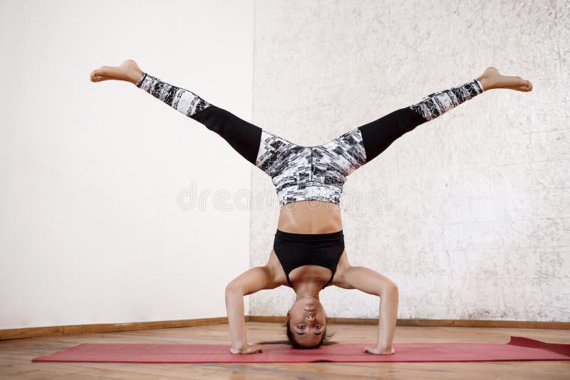 Muchacha atlética hermosa joven que practica asana interior de la posición del pino de la brazo-balanza de la yoga en la estera r fotos de archivo libres de regalías