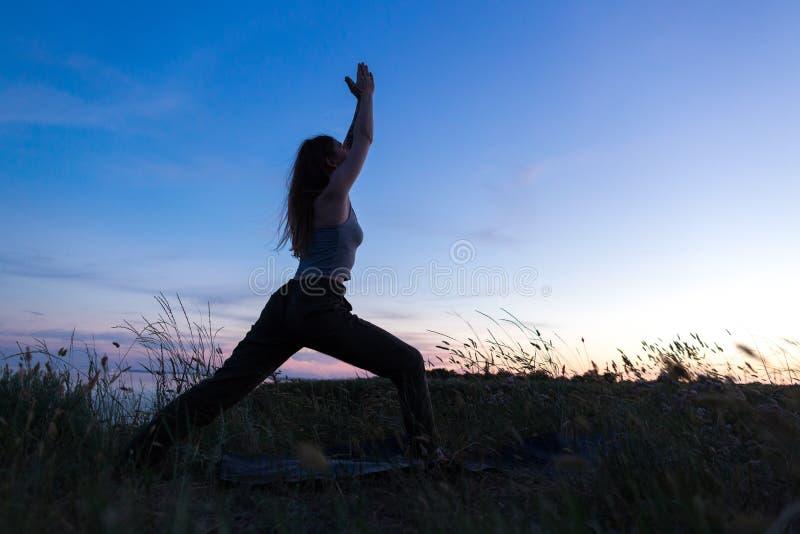 Muchacha atlética hermosa que hace yoga contra el mar fotografía de archivo libre de regalías