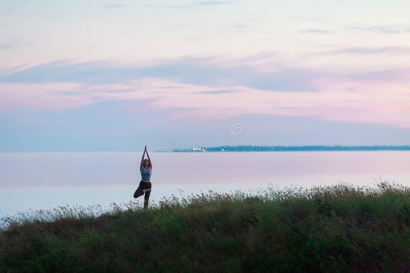 Muchacha atlética hermosa que hace yoga contra el mar foto de archivo
