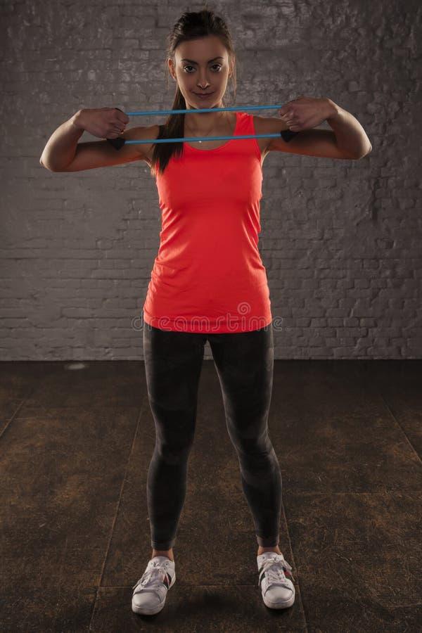 Muchacha atlética joven hermosa que ejercita con el caucho elástico fotografía de archivo