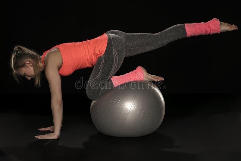 Muchacha atlética joven que ejercita con una bola de goma grande imagenes de archivo