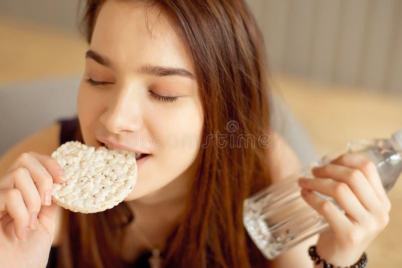 Muchacha atlética que come las tortas de arroz crujientes en sus manos que sostienen una botella de agua potable, comida sana, fo foto de archivo