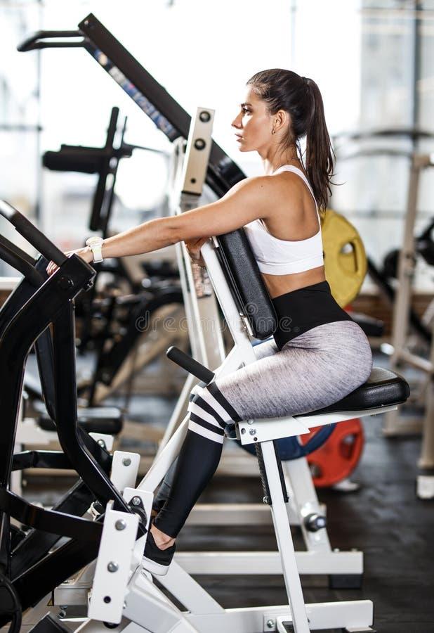 Muchacha atl?tica joven vestida en la ropa de deportes que hace ejercicios con el equipo de deporte especial en el gimnasio moder fotos de archivo