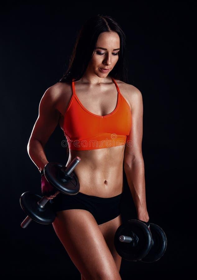 Muchacha atractiva agradable que hace entrenamiento con las pesas de gimnasia aisladas sobre fondo negro La mujer joven atlética  imágenes de archivo libres de regalías