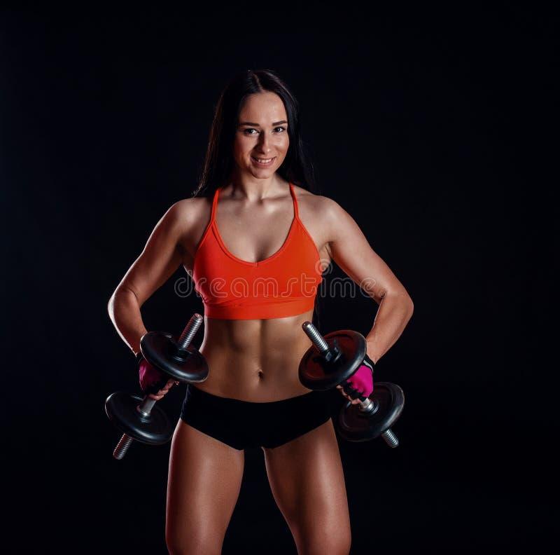 Muchacha atractiva agradable que hace entrenamiento con las pesas de gimnasia aisladas sobre fondo negro La mujer joven atlética  fotos de archivo