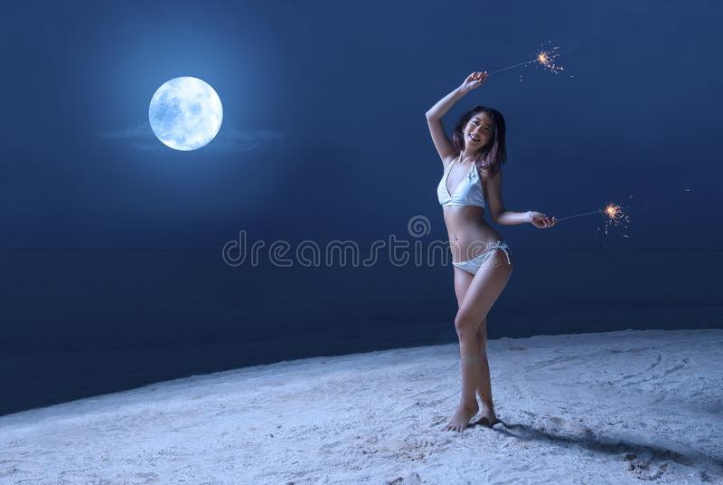 Muchacha atractiva asi?tica en el bikini que sostiene los fuegos artificiales en la playa en la noche imagenes de archivo