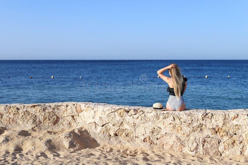 Muchacha atractiva atractiva caliente bonita hermosa que se relaja en traje de baño en piedras con el mar azul y cielo en fondo V imagenes de archivo