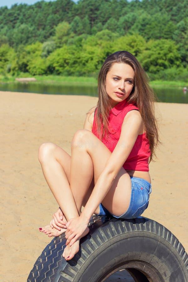 Muchacha atractiva con el pelo oscuro largo que se sienta en pantalones cortos en la playa en la rueda en un día soleado imagenes de archivo