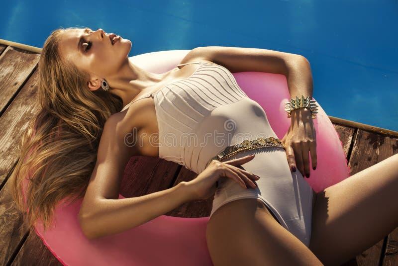 Muchacha atractiva con el pelo rubio en el bikini que se relaja al lado de una piscina imagen de archivo