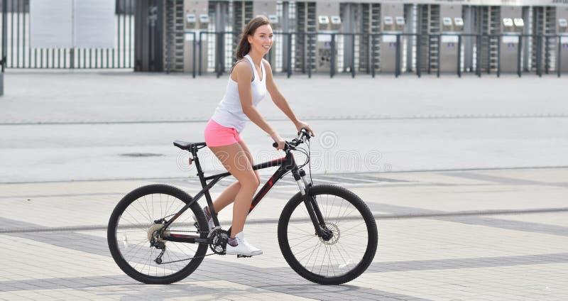 Muchacha atractiva con la bicicleta Mujer deportiva atractiva delgada joven en pantalones cortos rosados y risitas blancas de pel imagen de archivo