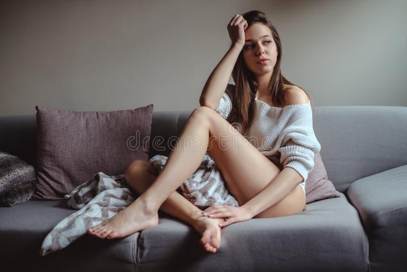 Muchacha atractiva con las piernas largas que se sientan en un sofá fotografía de archivo libre de regalías