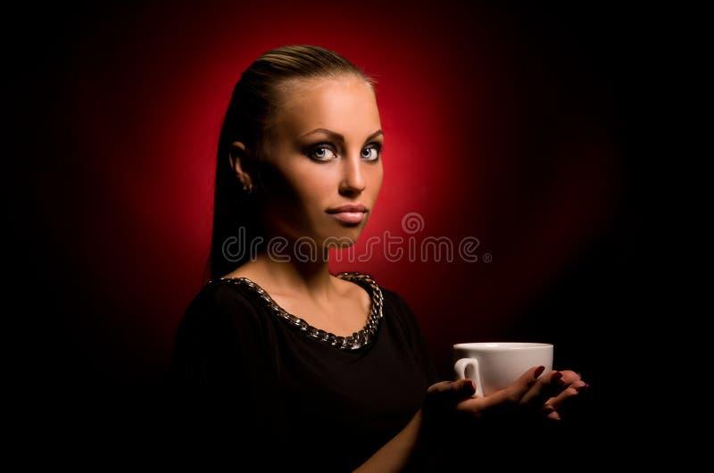 Muchacha atractiva con maquillaje agresivo y la taza blanca imagen de archivo libre de regalías