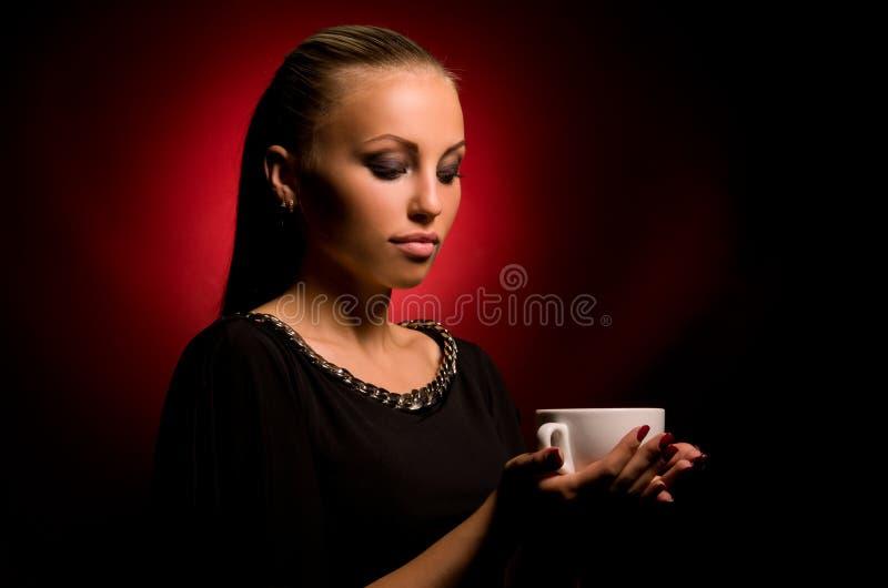 Muchacha atractiva con maquillaje agresivo y la taza blanca imagen de archivo