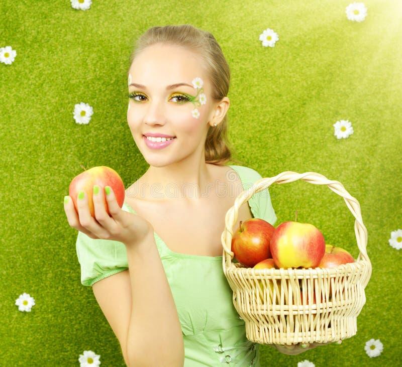 Muchacha atractiva con una cesta de manzanas imagenes de archivo