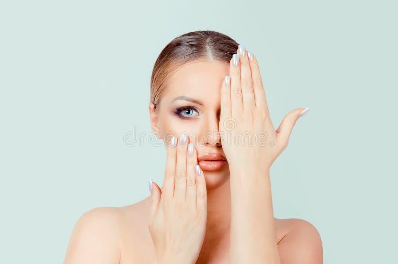 Muchacha atractiva de la belleza que muestra el maquillaje completo, labios rosados naturales, clavos beige fotografía de archivo libre de regalías