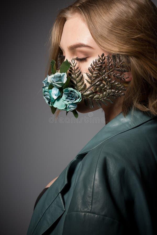 Muchacha atractiva de la moda con una máscara de la flor imagenes de archivo