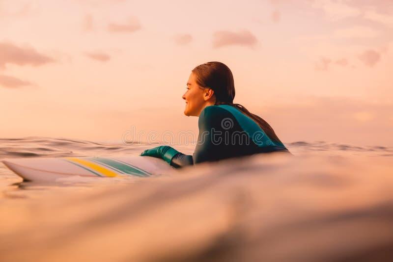 Muchacha atractiva de la resaca con el cuerpo perfecto en la tabla hawaiana en el océano El practicar surf en la puesta del sol fotografía de archivo