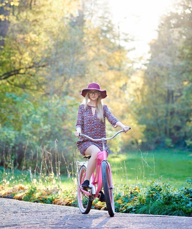 Muchacha atractiva de pelo largo de moda rubia en vestido corto con la bicicleta de la señora en parque soleado fotografía de archivo libre de regalías
